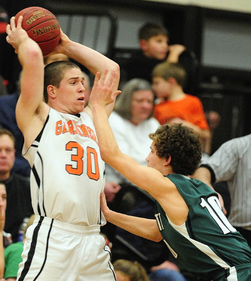 Gardiner's Dennis Meehan, left, looks for a teammate to pass to as Leavitt's Sam Green tries to block his view during a game on Friday at the James A. Bragoli Memorial Gym in Gardiner.