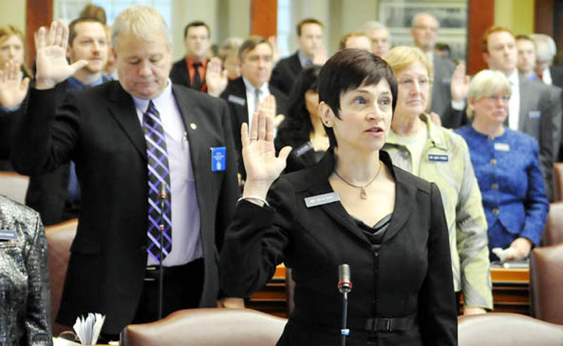 Gay Grant, D-South Gardiner, center, takes the oath of office as a state representative Wednesday at the State House. All Senate and House members were sworn in for the 126th Legislature by Gov. Paul LePage.