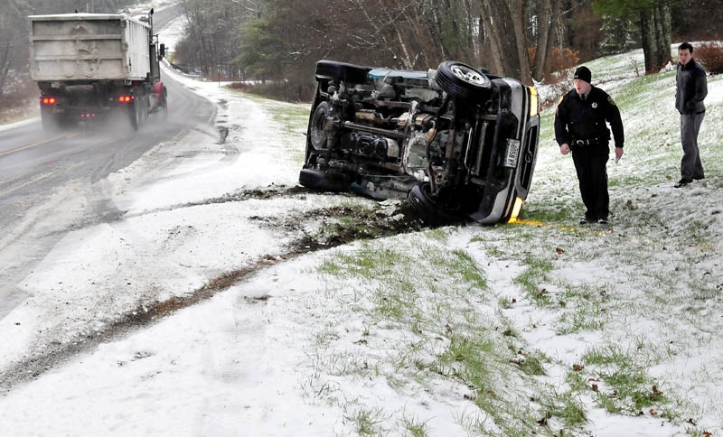 Kennebec County Sheriff's Office Deputy Jacob Pierce investigates a truck rollover, after the vehicle slipped off the ice- and slush-covered Route 139 in Benton, on Monday. The uninjured driver is at right.