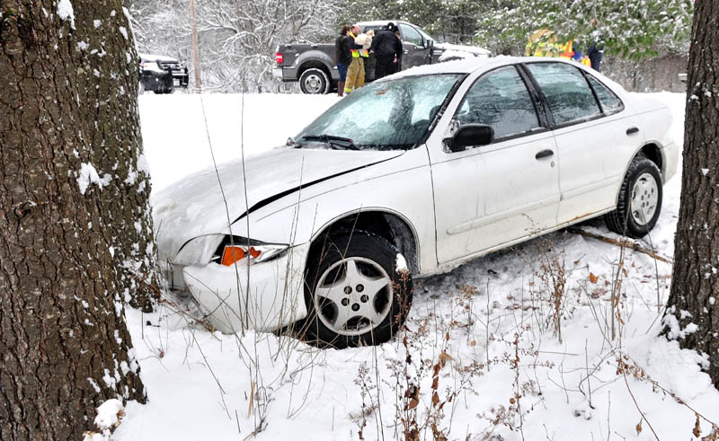 A Winslow firefighter cradles a dog as rescuers help an injured driver out of a vehicle that slid off snow-covered Route 100 in Winslow on Monday. The dog was a passenger in the vehicle and escaped injury.