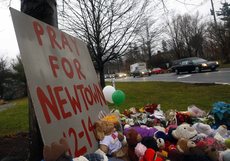 A hearse carrying the casket of of six-year-old Jack Pinto passes a makeshift memorial on its way to Newtown Village Cemetery in Newtown, Connecticut. (Reuters / Eric Thayer)