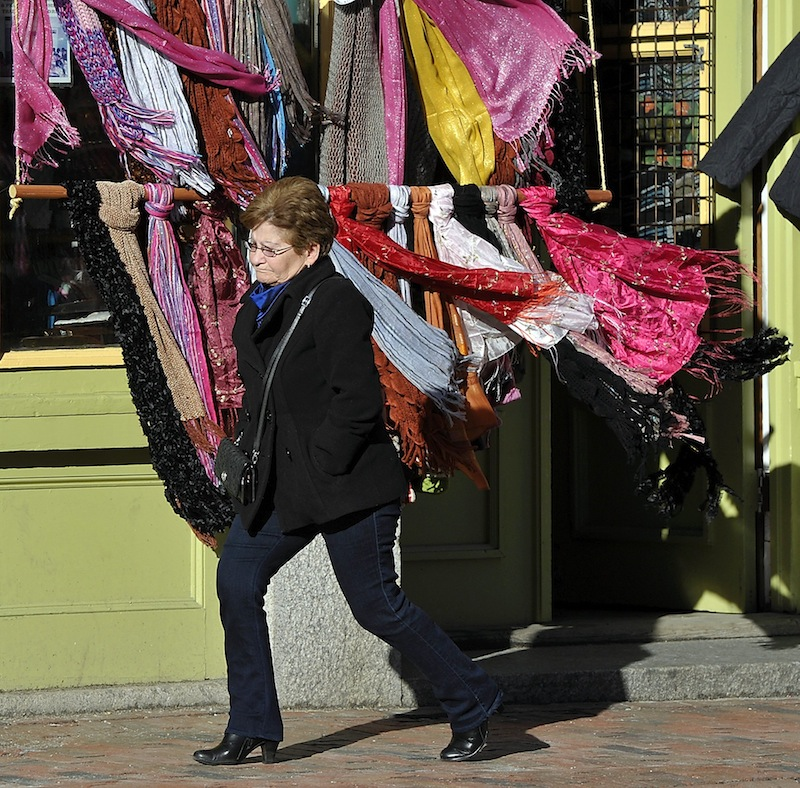 On Thursday, January 31, 2013, the wind blows hard on Fore Street in the Old Port as Pierrette Bolduc from Biddeford passes by a rack of blowing colorful silk and cotton scarves from Indonesia at Siempre Mas.