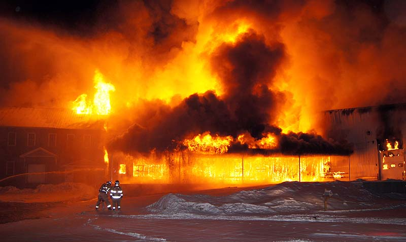 In this photo provided by Chuck Blaquiere, firefighters are dwarfed by a warehouse fully engulfed in flames behind a fireworks store in West Paris on Tuesday.
