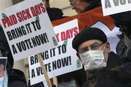 Activists hold signs Friday during a rally at New York's City Hall to call for immediate action on paid sick days legislation in light of the continued spread of the flu. An unusually early and vigorous flu season is drawing attention to the cause that has both scored victories and hit roadblocks in recent years: mandatory paid sick leave.