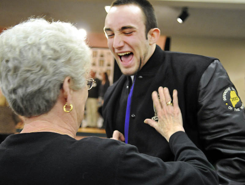 TAKE THAT: 2012 Gaziano Defensive Lineman award winner Kurt Massey, of John Bapst High School, laughs as his grandmother, Pat Massey, touches his award jacket Sunday in Augusta.