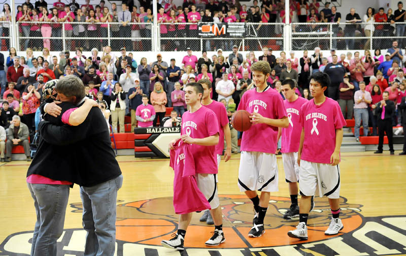 SUPPORT: Hall-Dale High School basketball players approach their former coach, Jim Patrick, as he hugs his wife, Cheryl, before a game Thursday in Farmingdale. The school held a fundraiser for cancer research. Cheryl Patrick is fighting cancer.