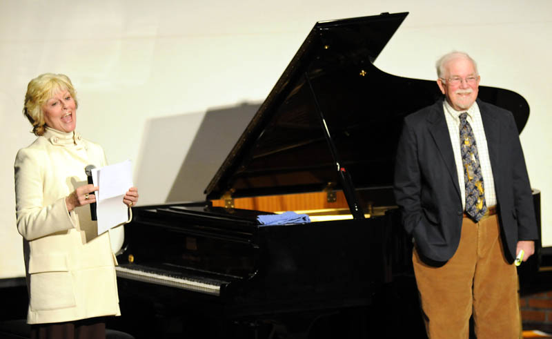 University of Maine at Augusta President Allyson Handley thanks the school's Senior College after Tom Feagin, a director at the Senior College, right, donated a piano to the University of Maine at Augusta on Sunday.