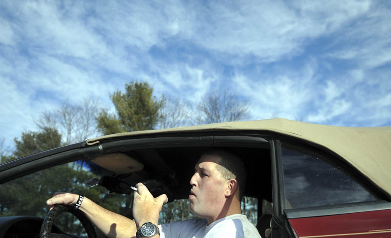 George Speck, of Augusta, smokes a cigarette Monday, in his car at the University of Maine in Augusta. A new policy at the school prohibits the use of tobacco products, except in private vehicles with the windows rolled up.