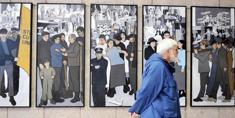 Ken Jones of Farmingdale on Monday examines the labor murals that are now hanging on the wall of the Cultural Building atrium that serves as the entryway to the Maine State Museum in Augusta.