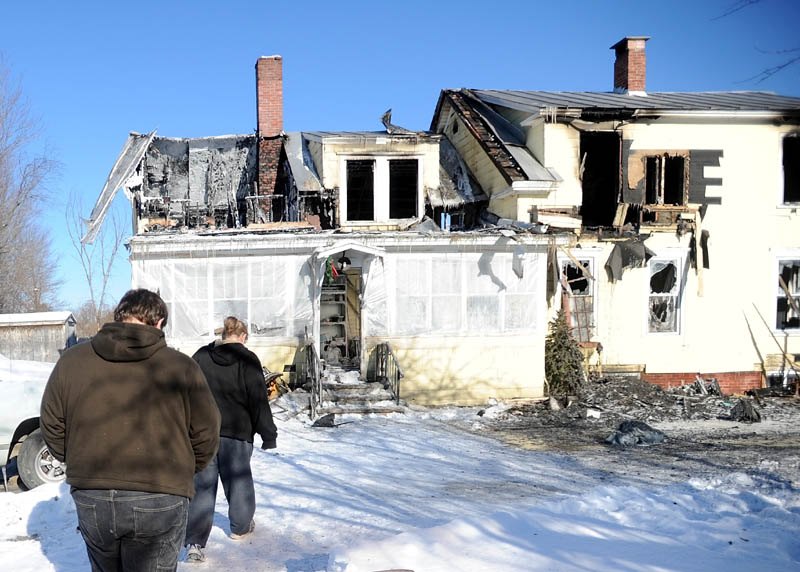 Cole Williams, 16, left, and his mother, Becky Williams, 40, tour what's left of a Madison Avenue home destroyed by fire around 3 a.m. Friday.
