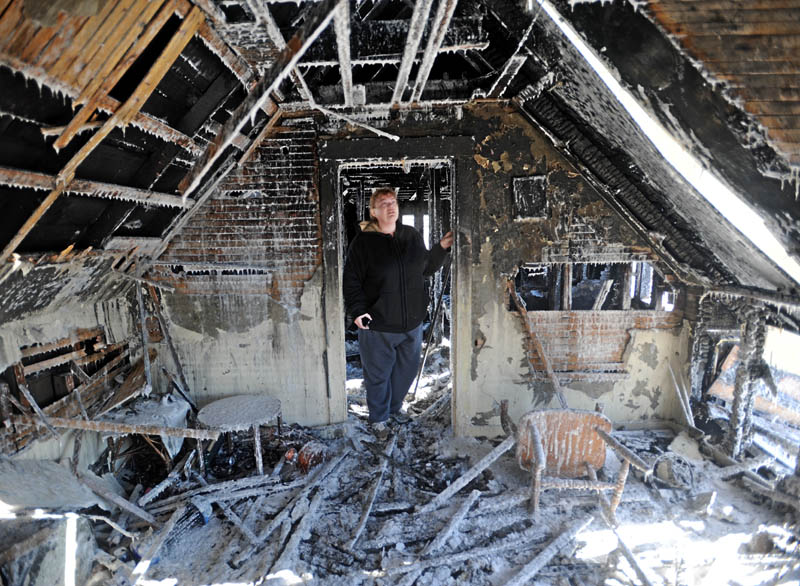 Becky Williams, 40, inspects the ice-covered walls of the second floor of her parents' Madison home, which was destroyed by fire around 3 a.m. Friday morning. Officials believe the fire started near this room, because of faulty electrical wiring.