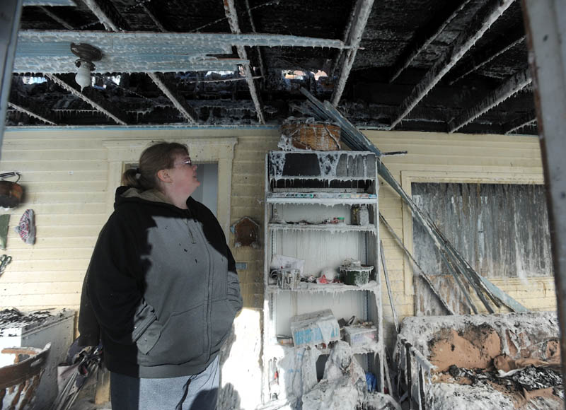 Becky Williams, 40, walks through the iced-over entry way of her Madison Avenue home in Madison after it was destroyed by fire around 3 am Friday. Six area fire departments responded to the blaze, as temperatures reached below zero degrees.