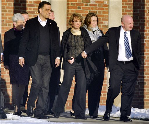 Former U.S. Rep. Gabrielle Giffords, center, holds hands with her husband, Mark Kelly, while exiting Town Hall at Fairfield Hills Campus in Newtown, Conn., after meeting with Newtown officials in this Jan. 4, 2013, photo.
