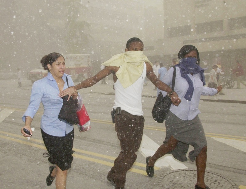 In this Sept. 11, 2001 file photo, three people may their way through a cloud of caustic dust after terrorists flew two airliners into the World Trade Center towers, bringing them down. The special fund set up by Congress to compensate people who fell ill after being exposed to ash and dust from the World Trade Center is making its first round of payments, more than two years after the money was appropriated. (AP Photo/Suzanne Plunkett, File)