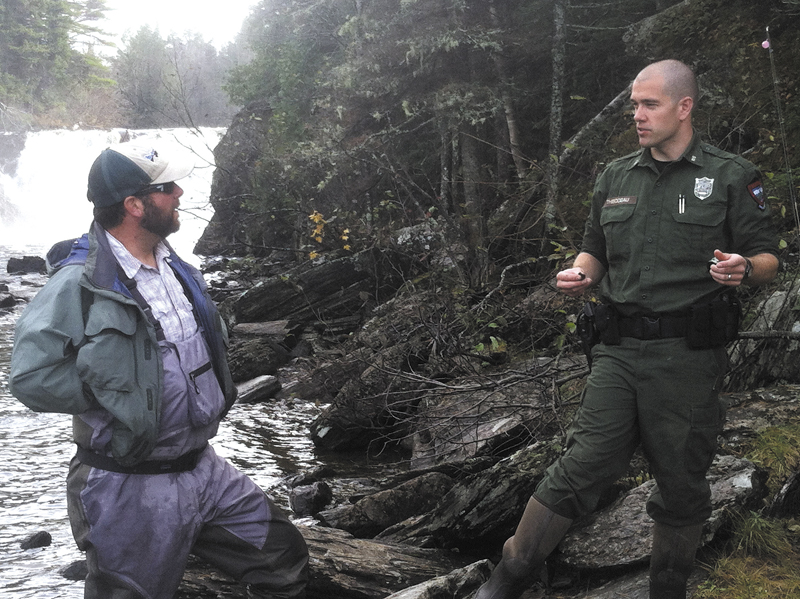 District Game Warden Troy Thibodeau, of Augusta, confers with fly fisherman Ryan Cote, of Monmouth, beneath Grand Falls on the Dead River in an unorganized township in Somerset County. Thibodeau is featured in the television series