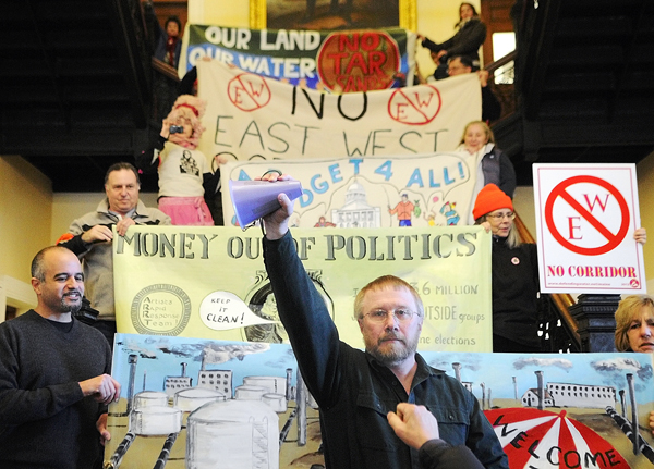 Staff photo by Joe Phelan Lew Kingsbury, of Pittston, holds up a megaphone after giving a speech on the steps in the Hall of Flags of the State House in Augusta on Tuesday January 8, 2013. The Alliance for Common Good, featuring members of 20 interest groups, joined together for to hold a