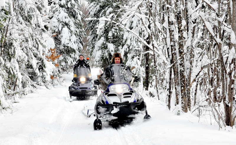 Ernie Rice, front, and Dennis Harris, both members of the Belgrade Draggin Masters club, groom snowmobile trails through the woods on Dec. 30.