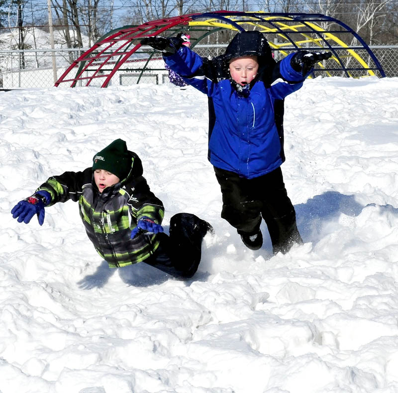 George J. Mitchell School students Jaimin Romagno, left, and Josh Vashon joyfully dive into the snow during recess on Monday in Waterville. School policy allows children to play outdoors if temperatures are 10 degrees F or higher.