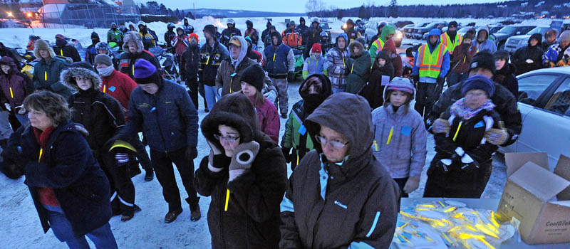 People gather and try to stay warm during a prayer, at the Torch Light Snowmobile Safety Vigil in Rangeley on Friday night.