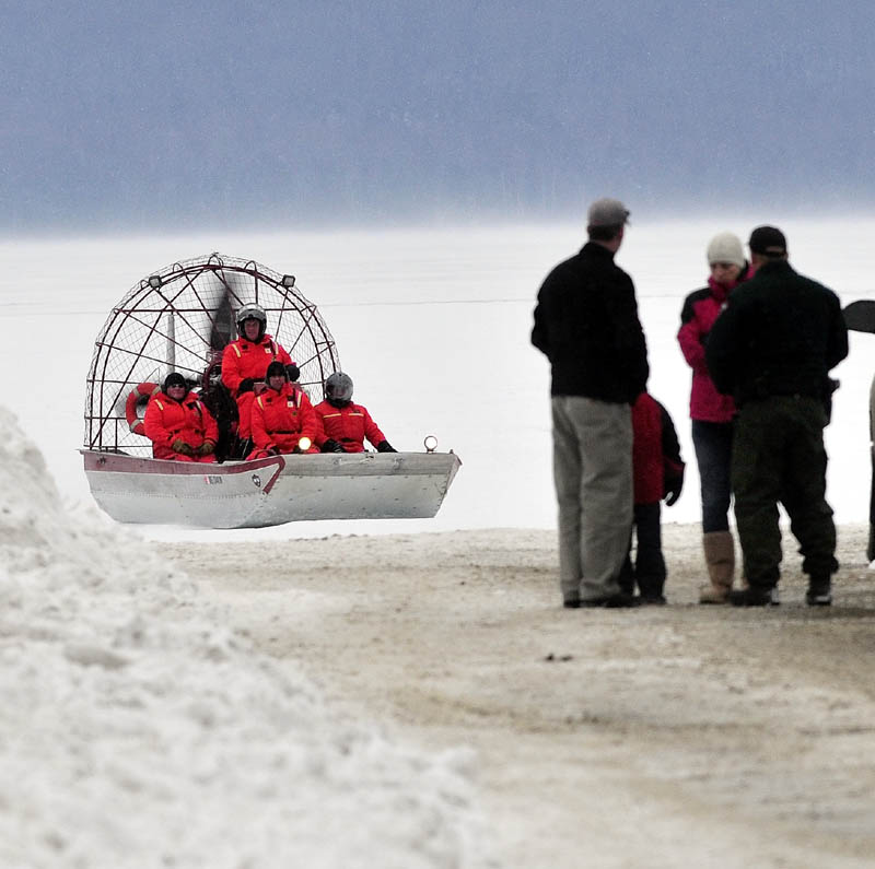 Maine Warden Service personnel return to shore in an airboat on Rangeley Lake on Dec. 31, after motoring over ice in search of three snowmobilers missing and presumed drowned in the lake. Wardens will use a remotely controlled underwater vehicle -- basically, a mini-submarine -- to resume the search, a warden service spokesman said on Monday.