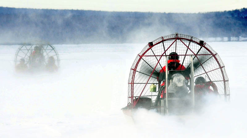 Two Maine Warden Service air boats head out on the ice on Rangeley Lake in Rangeley earlier this month to the open water location where four snowmobiles went through the ice on Dec. 30.