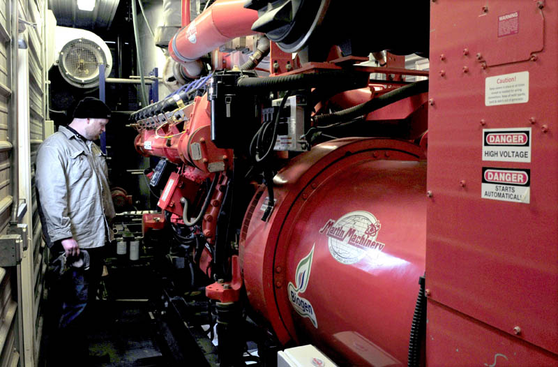 John Wintle monitors the engine inside the control room, where gas produced by mixing cow manure and food waste powers a generator and produces 5.2 million kilowatt-hours of electricity, at the Stonyvale Farm in Exeter.