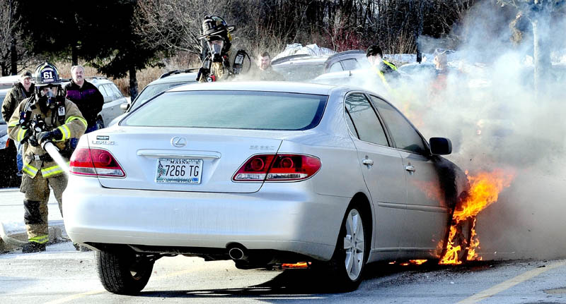 Waterville firefighters extinguish a fire that destroyed a 2005 Lexus sedan parked at Marden's Surplus and Salvage, at 458 Kennedy Memorial Drive in Waterville, on Monday. Owner Lucille Roberge of Waterville said the car, which she recently purchased, was insured.