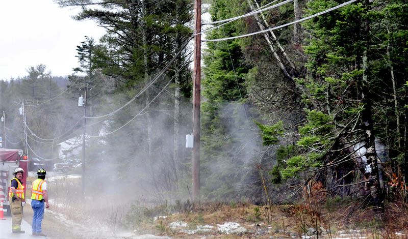 Winslow firefighters monitor a fallen tree leaning against a power line on China Road on Thursday morning. The tree smoked at the top where it hit the lines and at the base where the electricity was grounded.