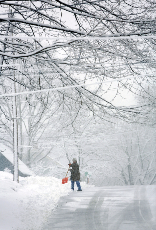 Kim Conley chops the snow while clearing the end of her driveway on Clemons Street in South Portland during the heavy snowfall Sunday morning.