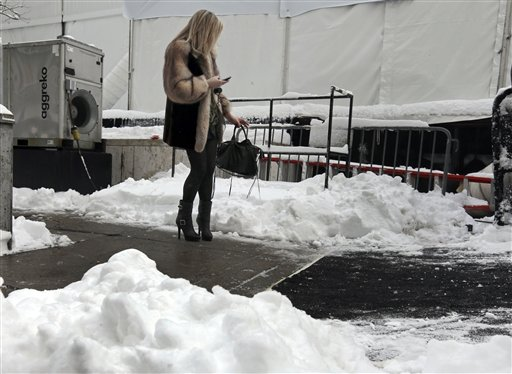 A woman checks her mobile phone outside Lincoln Center, home of New York's Fashion Week shows, Saturday, Feb. 9, 2013. In New York City, the snow total in Central Park was 8.1 inches by 3 a.m. (AP Photo/Richard Drew)