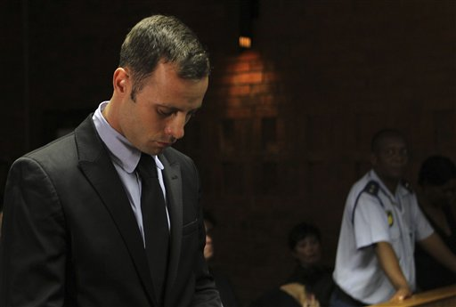 Olympic athlete Oscar Pistorius stands inside the court as a police officer looks on during his bail hearing at the magistrate court in Pretoria, South Africa, on Wednesday. A South African judge says defense lawyers will need to offer