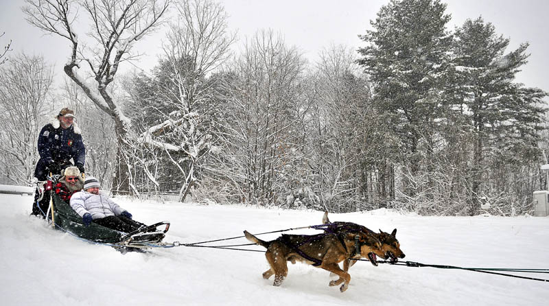 Kevin Quist, of Augusta, gives Sue, front, and Tim Stiefel, of Winthrop, a ride in a dog sled Sunday at Viles Arboretum in Augusta. The dogs are scheduled for two more pulls this year for guests at the arboretum.