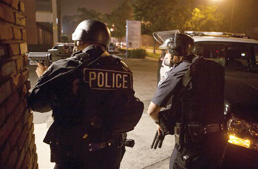 Police respond in Riverside, Calif., early Thursday morning, in search of the former LAPD officer accused of killing one police officer and critically wounding another.