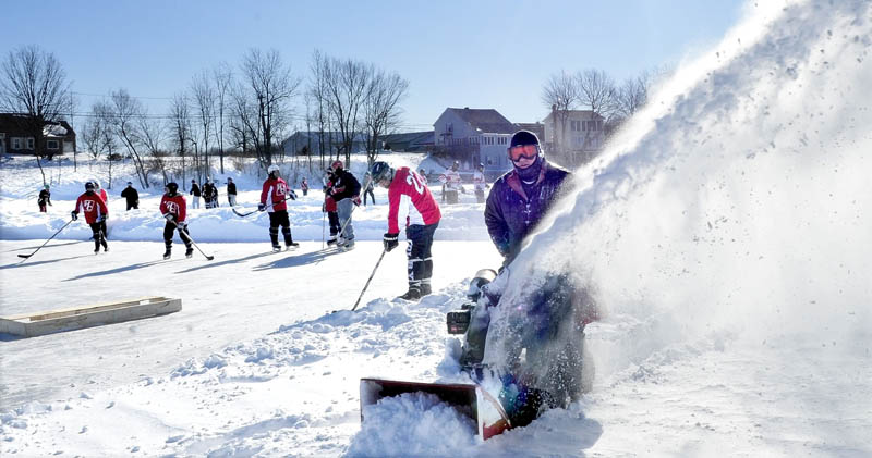 ICE WELCOME: Volunteer Bert Languet of Belgrade clears snow off the ice on China Lake for one of four rinks for the Maine Pond Hockey Classic on Sunday.