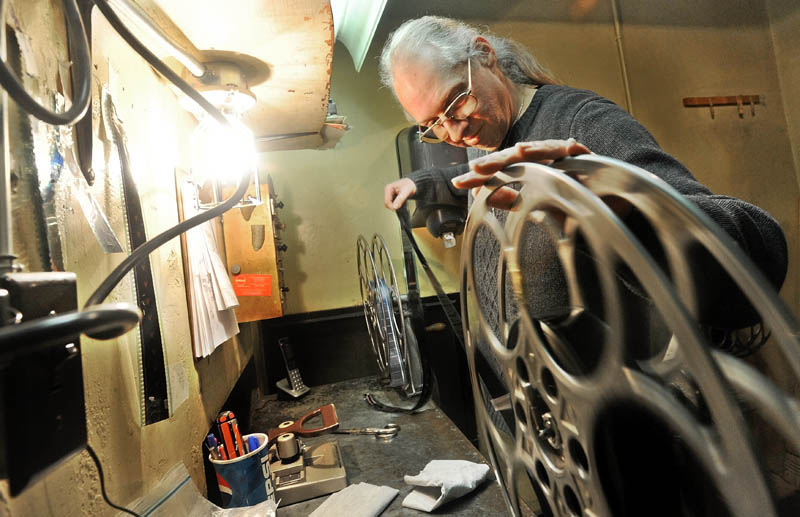 Bill Lashon winds 35 mm film manually in the projection booth at the Pittsfield Community Theatre on Main Street Thursday. The movie industry is shifting from the 35 mm film to digital by the end of the year.