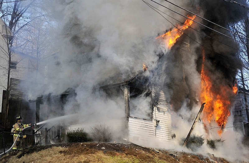 Firefighters battle a blaze on Squire Street in Waterville Thursday.