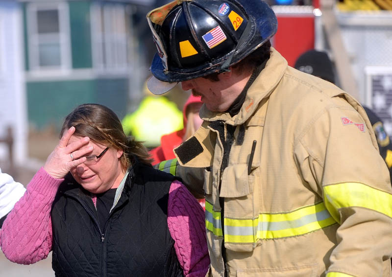 Kimberly Guite, 46, is comforted by Lt. Scott Holst, right, as her rental home burns on Squire Street in Waterville Thursday.