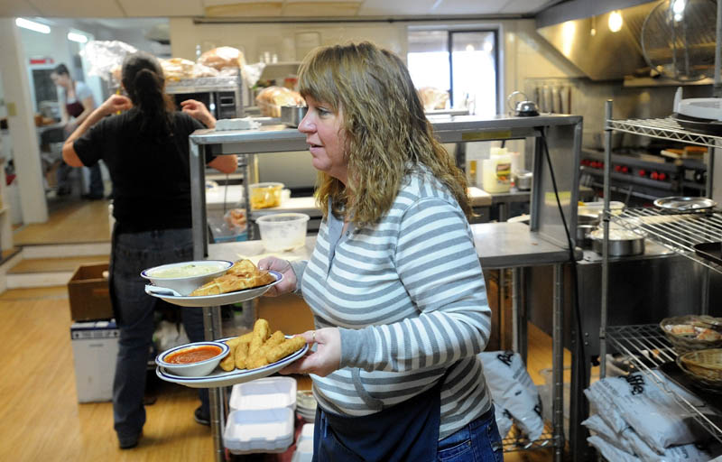 Shelly Stevens, former owner of Thompson's Restaurant, along with her husband, Parker, carries orders from the kitchen to patrons on Wednesday. Stevens still works as a waitress for the new owners of Thompson's Restaurant.