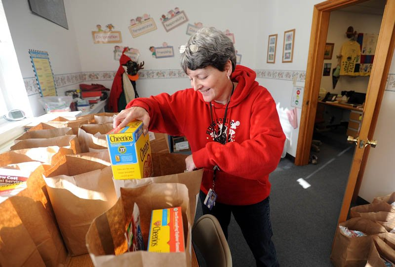 Denise Kimball, principal at Hartland Consolidated School, packs snack bags recently, to be distributed to families to help meet the nutritional needs of children over February break.