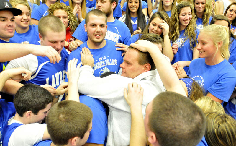 THANKS: Lawrence High School basketball coach Mike McGee has a group hug with the Rowdies, Lawrence's student cheering section prior to the Bulldogs game against Skowhegan on Thursday. McGee, who is retiring after the season, was honored before the game.