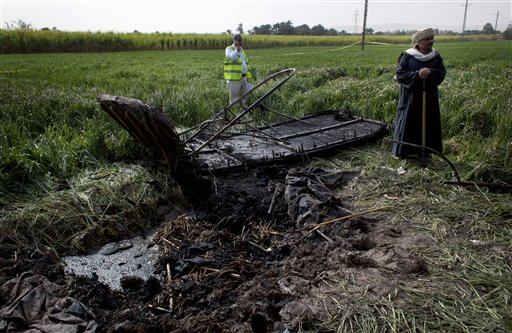 An Egyptian inspector of the Civil Aviation Authority, left, works at the site of the balloon accident, in Luxor, Egypt, Tuesday. A hot air balloon flying over Egypt's ancient city of Luxor caught fire and crashed into a sugar cane field on Tuesday, killing at least 19 foreign tourists in one of the world's deadliest ballooning accidents and handing a new blow to Egypt's ailing tourism industry.