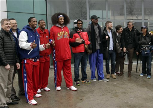 Flamboyant former NBA star Dennis Rodman, fifth from right, poses with three members of the Harlem Globetrotters basketball team, in red jerseys, and a production crew for the media upon arrival at Pyongyang Airport, North Korea, Tuesday, Feb. 26, 2013. Rodman known as