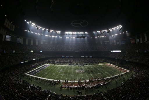 Fans and members of the Baltimore Ravens and San Francisco 49ers wait for power to return in the Superdome on Sunday, Feb. 3, 2013, during an outage in the second half of the Super Bowl.