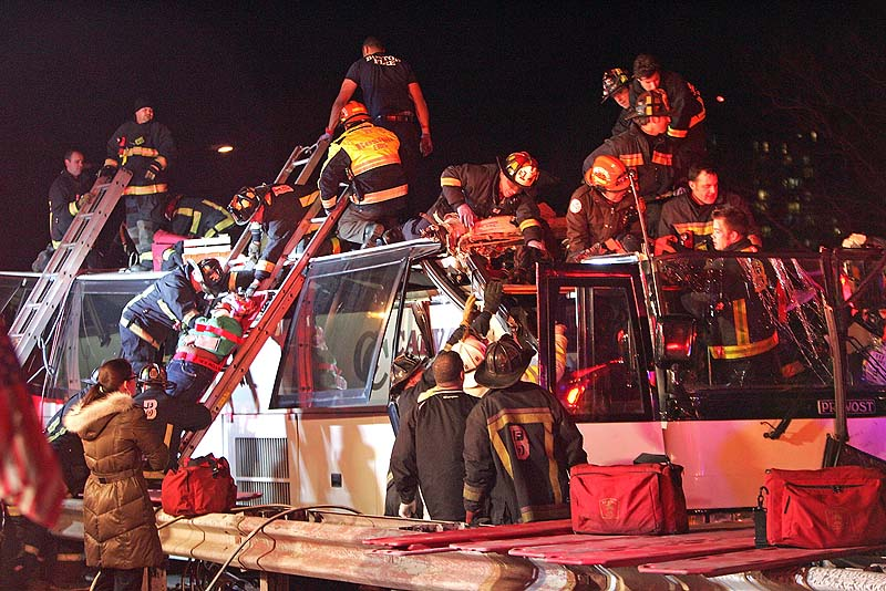 Emergency personnel remove passengers at the scene of a bus crash Saturday in Boston. Authorities say a charter bus heading from Harvard University to Pennsylvania struck a bridge in Boston, injuring 33 people.