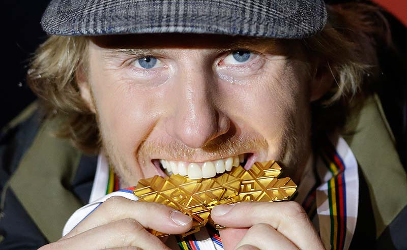 Ted Ligety, of the United States, takes a bite out of his gold medal in the giant slalom. Ligety won three golds at the Alpine skiing world championships in Schladming, Austria.