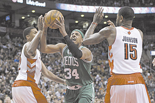 HERE I COME: Boston's Paul Pierce, center, drives to the basket as Toronto's Amir Johnson, right, and Rudy Gay defend during first-half action Wednesday in Toronto.