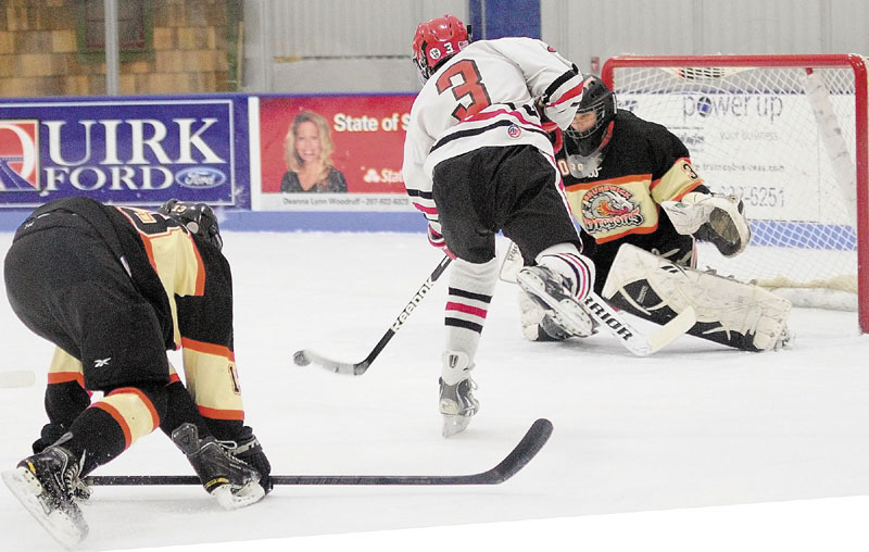 Cony's Dallas Clark, center, gets past Brunswick defenseman Tyler Sullivan, left, to shoot and score on Brunswick keeper Blake Alexander to tie the score 1-1 in first period of a hockey playoff game on Tuesday February 26, 2013 at the Bank of Maine Ice Vault in Hallowell.