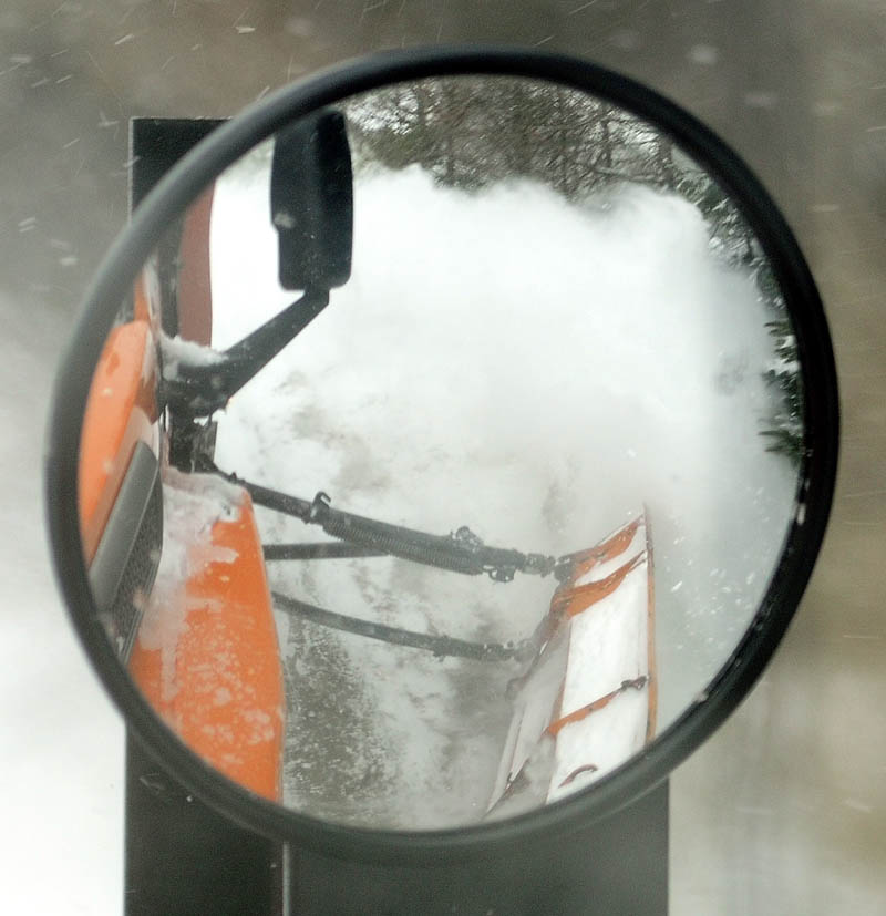 A reflection in mirror snow flying of the wing plow, on the side of the truck driven by Augusta Public Works plow truck driver Stan Moore, on Saturday.