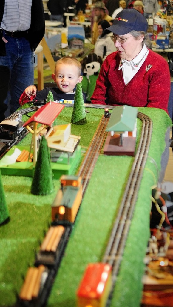 Connor Ruttenberg, 2 1/2, of Turner, pushes the buttion to unload logs from a model train with some help from Joanne Burns, of Friendship, at the Maine 3-Railers display on Saturday, during the Whitefield Lions Club Model Railroad & Doll House Show at the Augusta armory.