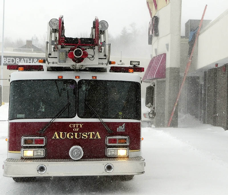 Augusta's ladder truck sits in front of Turnpike Mall, off Whitten Road in Augusta, as an Augusta Fuel Co. technician climbs onto the roof to check the heating system, around 3:20 p.m. on Saturday. The fire department responded to call about high carbon monoxide levels in the building.